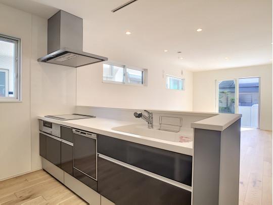 食洗器付きのキッチン。LDKが見渡せます。背後には天井までの棚が備え付けられ、収納力があります。