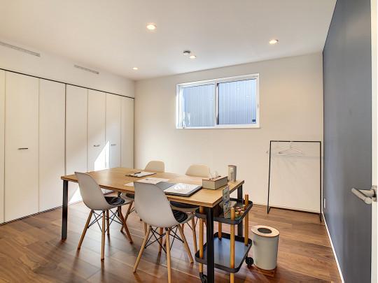 落ち着いた壁紙の寝室は、モデルルームの商談スペースとして利用中。