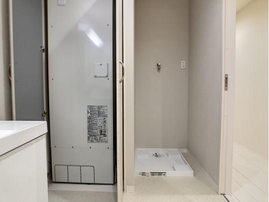 洗面室には洗濯機スペースがあり、電気温水器スペースには収納扉があります