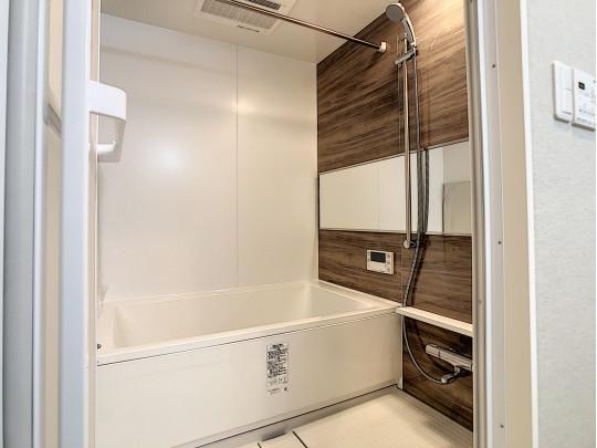 ブラウンの一面壁が落ち着く雰囲気の浴室で、日々の疲れが癒されます