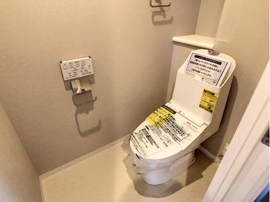 こちらも新品交換済みのトイレです。手洗い、タオルハンガー、飾り棚を備えた余裕ある空間です