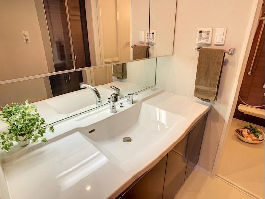 鏡面裏にも収納のある洗面室です。キッチン、浴室とブラウンで合わせ、統一感ある落ち着いた雰囲気です
